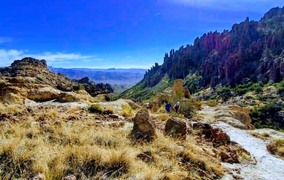 man and woman hiking up a trail in the mountainous Arizona desert