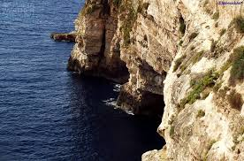 The blue Mediterranean Sea with Ghar Hasan cave set in the sheer cliff.