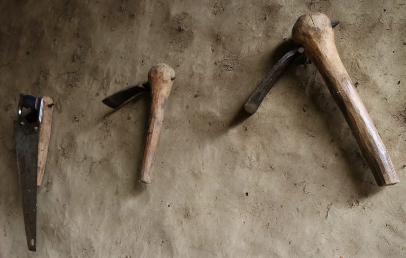 tools of the trade hanging from a mud wall Lawra