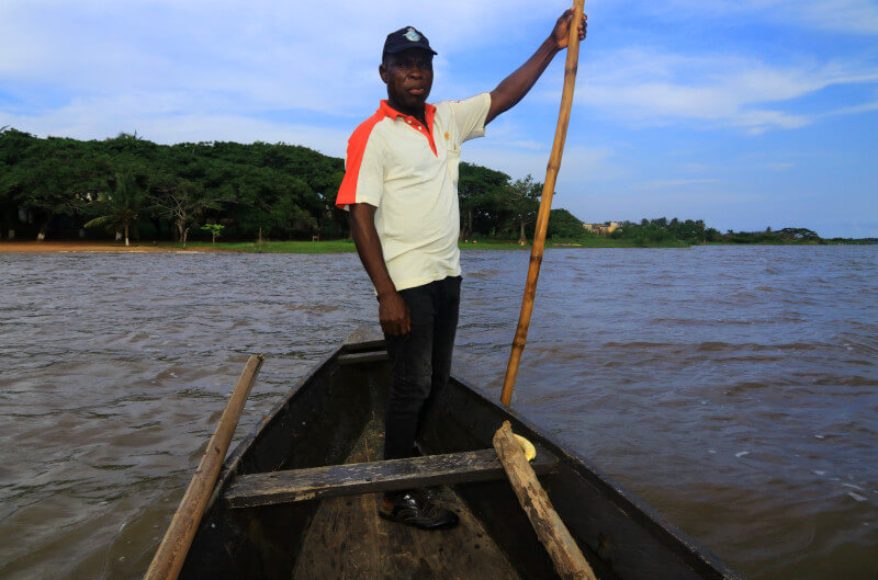 Capitain punting across Lake Togo on his pirogue