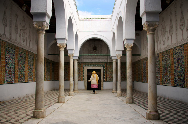 Lady walking through columned Mosque of the Barber Kairouan Tunisia