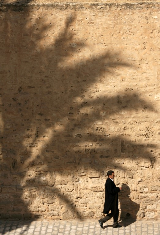 Local walking past a large shadow of a palm tree Sousse