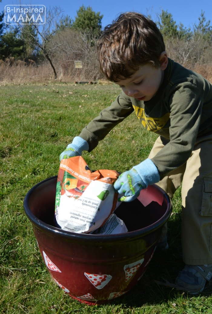 Planting a Pizza Garden in a DIY Pizza Garden Planter - JC Adding the Potting Mix - at B-Inspired Mama