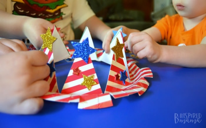 An Easy 4th of July Craft for Kids - A Stars and Stripes Crown - Everyone adding the star stickers - at B-Inspired Mama
