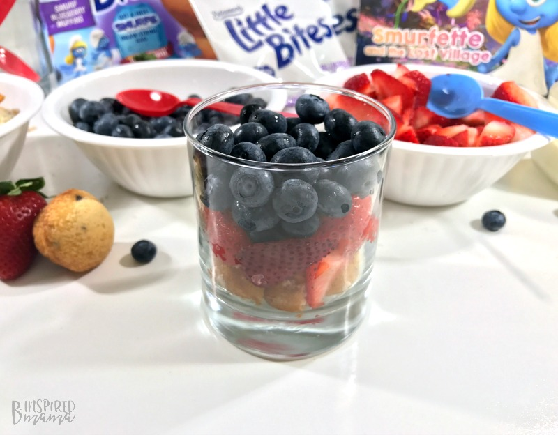 Adding layers of fruit to Super Fun Smurf Blueberry Muffin Parfait Recipe