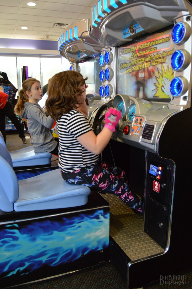 Priscilla and her friend loving the racing game at her Chuck E. Cheese's Birthday Party + Birthday Traditions for Kids - at B-Inspired Mama