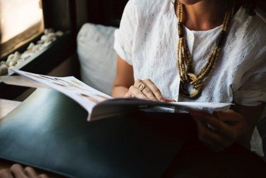 Eine sitzende Frau im weißem T-Shirt, dessen Kopf und Beine man nicht sieht, hält eine Zeitschrift vor sich offen. Die Frau hat eine auffällige Kette und einen Ring an. Das Bild transportiert eine erhabene Stimmung.