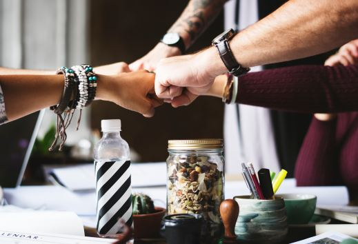 Über einem Tisch, wo vermutlich ein Meeting gerade stattfindet, kommen fünf Fäuste zusammen. Die Arme sehen ganz unterschiedlich aus - verschiedene Hautfarben, Frauen und Männer Arme, mit und ohne Uhr, mit und ohne Armbänder etc.