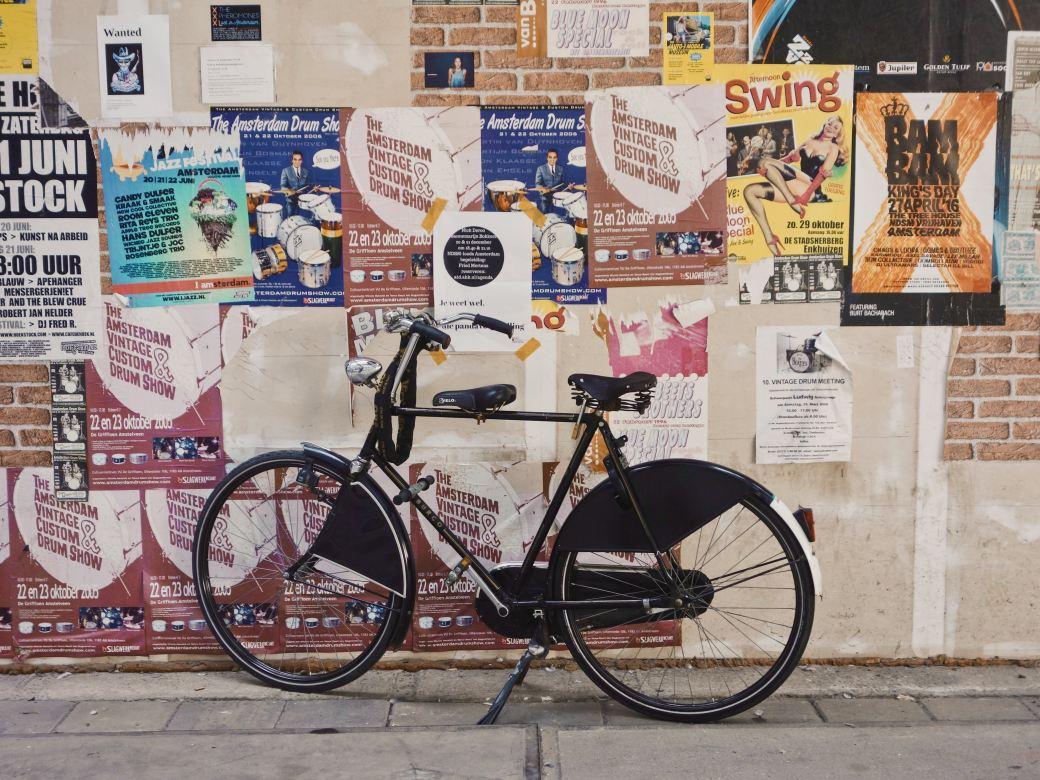 Auf dem Bild ist eine Backseiten- und Betonwand zu sehen, auf der verschiedene Werbeposter aufgeklebt sind. Es herrscht eine große Unordnung auf der Wand - manche Poster kleben dort mehrfach, andere sind zerrissen. Vor der Wand parket ein schwarzes Männer Fahrrad.