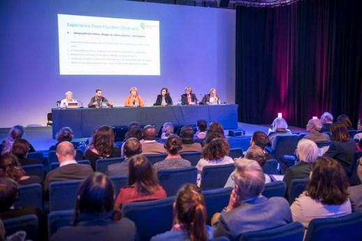 Das Bild zeigt einen abgedunkelten Raum. Im Hintergrund wird eine Präsentation auf einer Leinwand gezeigt. Es sitzen 6 Präsentatoren auf einem Podium und circa 20 Personen, die zuhören. Der Raum wirkt voll, da nur ein Teil des Publikums gezeigt wird.