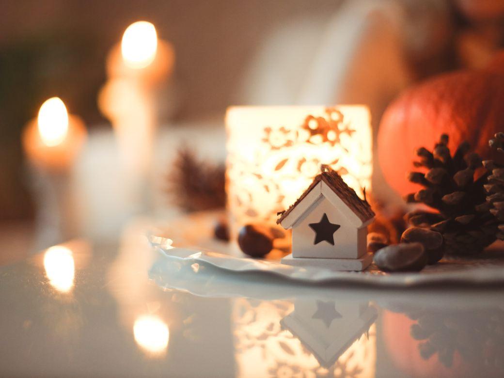 Das Bild zeigt eine winterliche und weihnachtliche Stimmung. Auf einem weißen Tisch steht ein feines Prozelangedeck mit einer Kerze, einem Häuschen, Kastanien und Tannenzapfen. Im Hintergrund schimmert es organ und es sind weitere Kerzen zu erahnen.