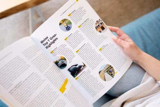 """Im Zentrum des Bilds steht ein aufgeklapptes Magazin. Zu lesen ist: """"Meine Top 7 Graz-Highlights"""". Auf einem Bild ist eine Rollstuhlfahrerin zu erkennen."""
