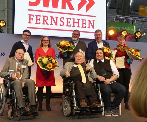 """Das Bild zeigt die Preisverleihung des Goldenen Rollstuhls. Die vier Preisträger haben große, bunte Blumensträuche in den Händen und zeigen ihre Urkunden. Zwei Rollstuhlfahrer, die den Preis verliehen haben sind ebenfalls auf dem Bild. Im Hintergrund ist ein Anbschnitt des Schriftzugs """"SWR Fernsehen"""" zu erkennen."""