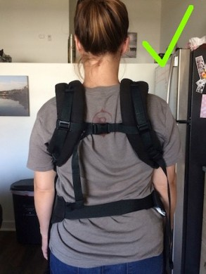 Baby carrier straps closer to make neck feel better with arrow