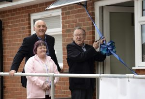 Peter cutting the ribbon to declare The Woodlands open (L to R) Peter Howell (Carer) with scissors next to his wife Val (Client) & David Chater (Chair of the Trustees at Headway Birmingham & Solihull) behind