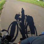The shadow of a touring cyclist.