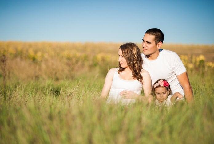 fiatal pár kislánnyal üldögél a mezőn a fűben