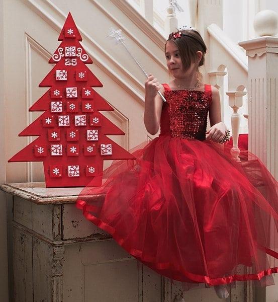 lépcső alján ül egy kislány gyönyörű piros ünnepi ruhában