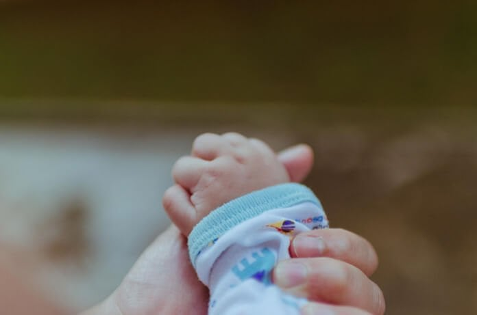 csecsemő kezecske anyukája kezében