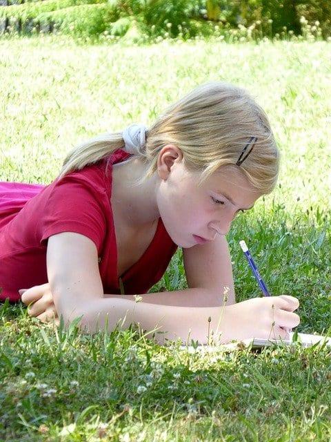 kislány fekszik a fűben és naplót ír