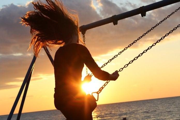 nő hintázik a lemenő nap fényénél