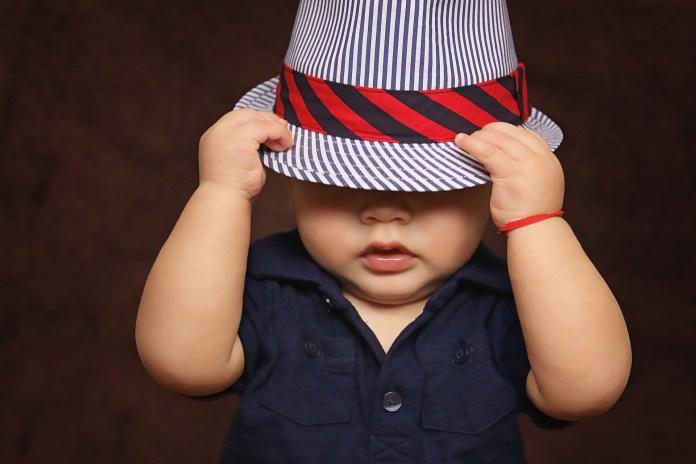 Kisfiú, aki a fejébe húzott egy kalapot.