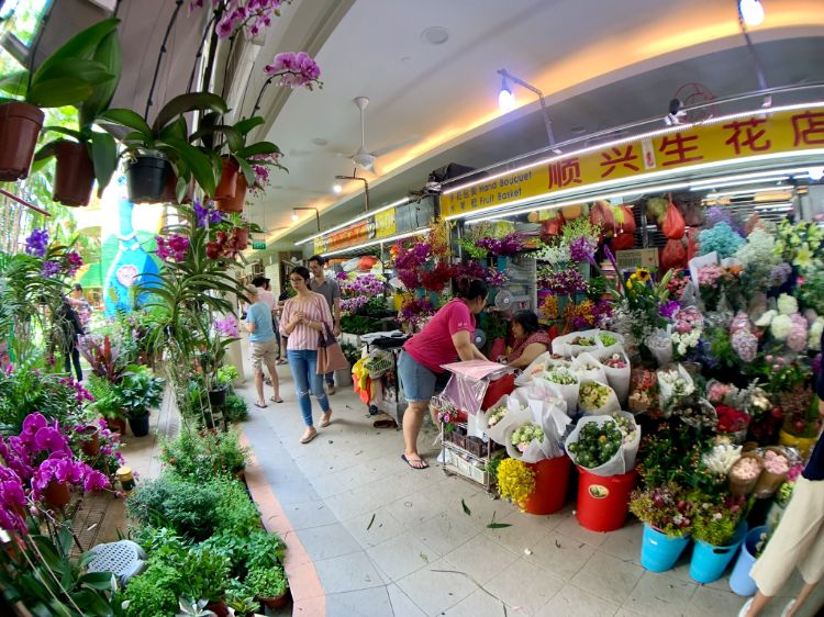 Ladies walking through a flower shop at Tiong Bahru Market
