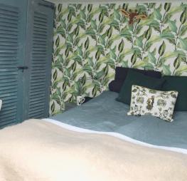 mooie papiermache giraf dierenkop op muur met palmbladerenbehang in slaapkamer