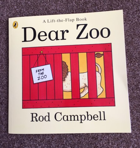 """The front cover of """"dear zoo' lift-the-flap book with a pale yellow background and an illustration of A lion partially obscured in a red cage with a note saying 'from the zoo' - by Rod Campbell"""