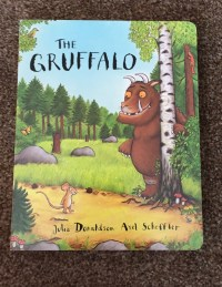The front cover of The Gruffalo board book by Julia Donaldson and Axel Sheffler with an illustration of a wood and a little mouse and the gruffalo