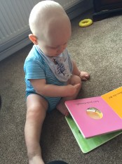 Almost bald, blond baby in a blue stripe vest and grey bib with his hand on an open book