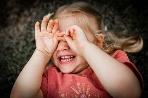 Petite fille se cache les yeux en souriant