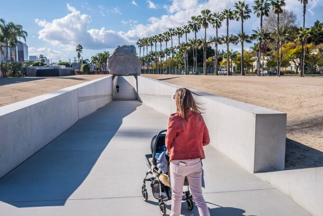 Long haul with a baby: A woman pushes a pram outside LACMA in LA © Steve Pretty
