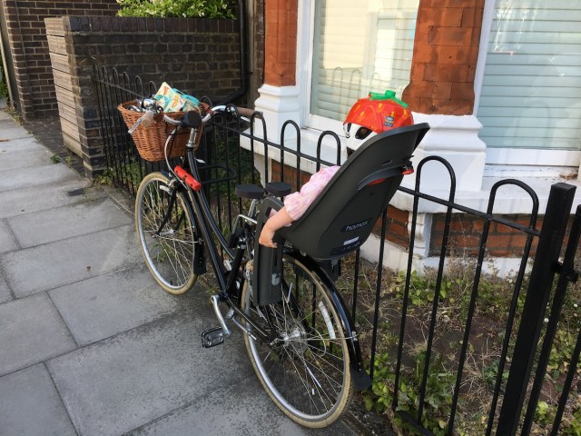 A toddler sleeps in a baby bike seat locked to some raillings