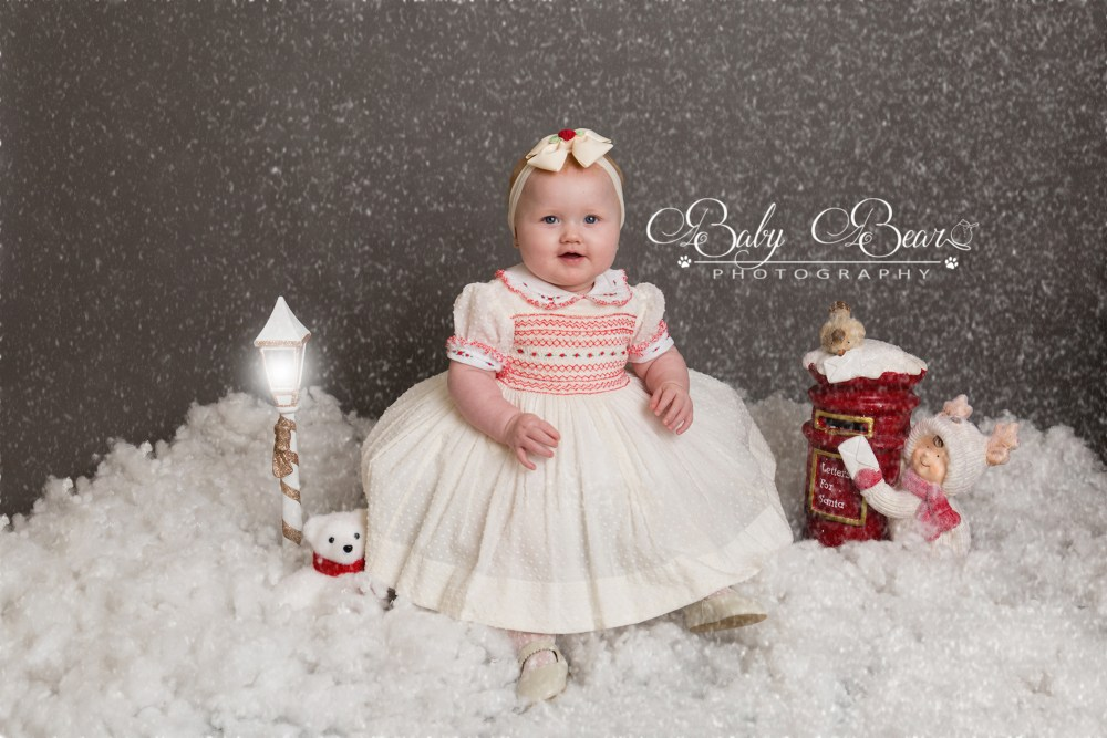 Baby in white dress in pretend snow shoot