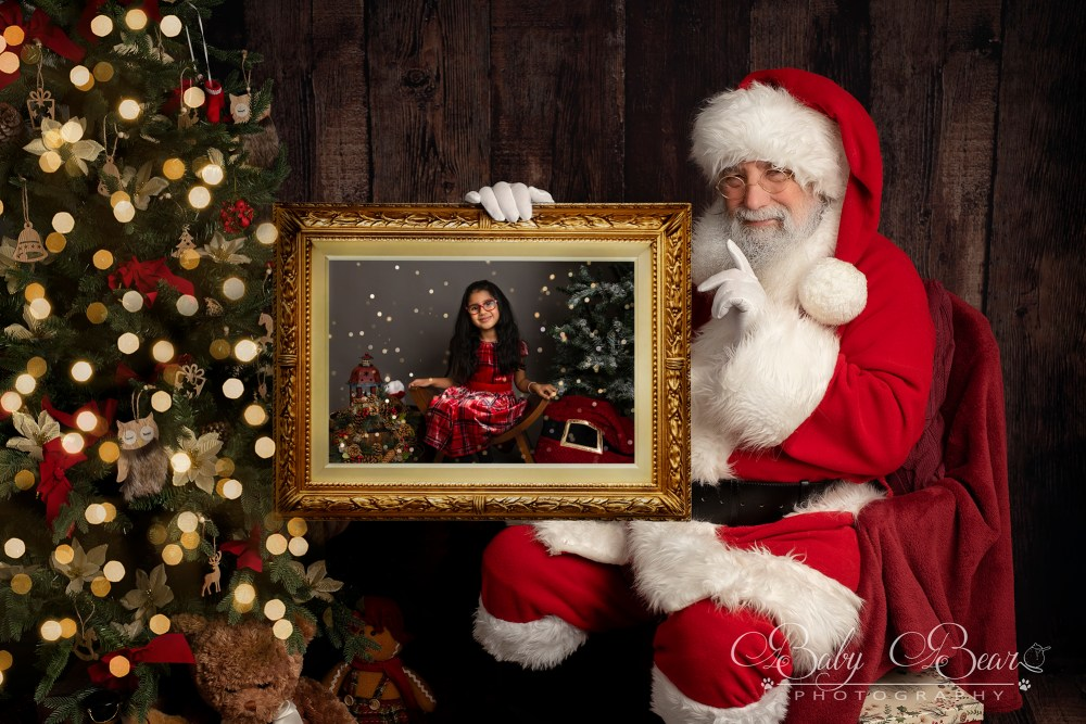Santa holding picture of girl in Coventry Christmas shoot