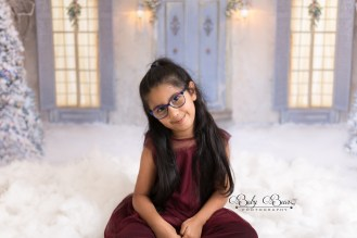 Little girl with glasses in christmas photoshoot with snow
