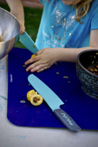 Kids cutting loquats for sorbet with playful chef safety knives