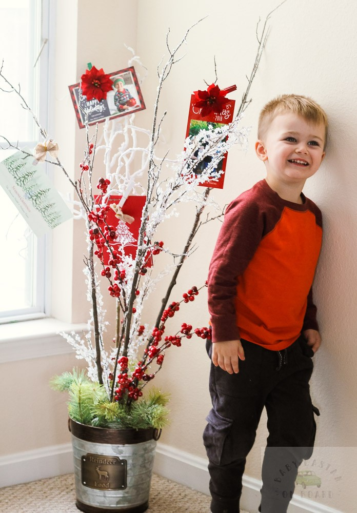 How To Make a DIY Christmas Card Holder Tree featured by top DC lifestyle blog, Baby Castan on Board: image of a Christmas card holder tree and a child looking at the Christmas cards on the tree