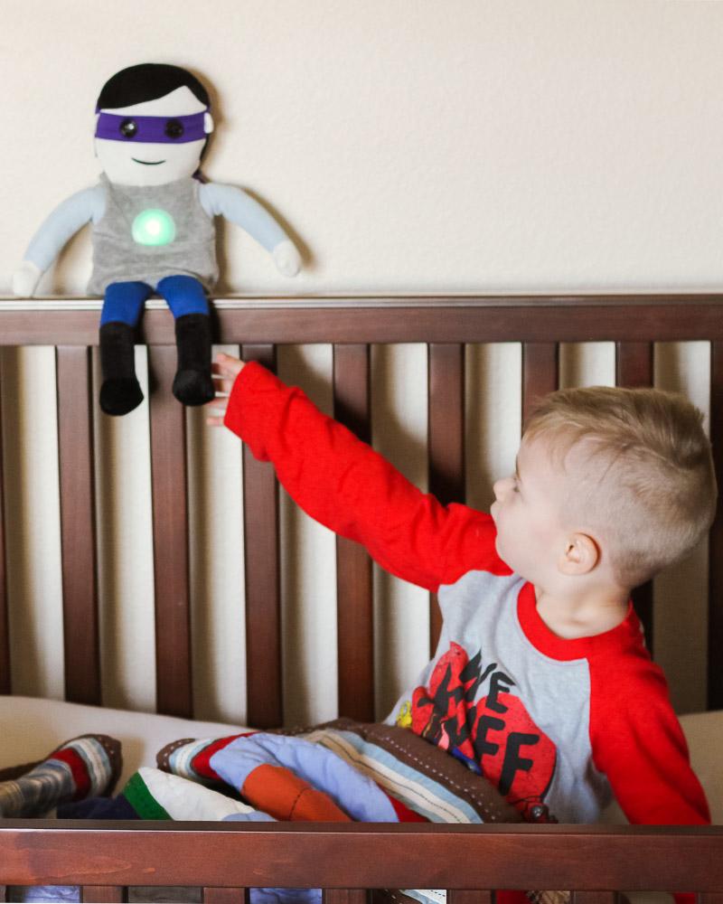 Toddler Crib_toddler reaching for sleeper hero doll