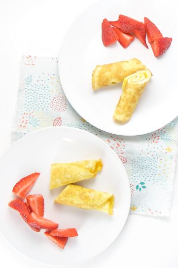 2 white round plates filled with an egg roll-up and strawberries, sitting on a multi colored napkin.