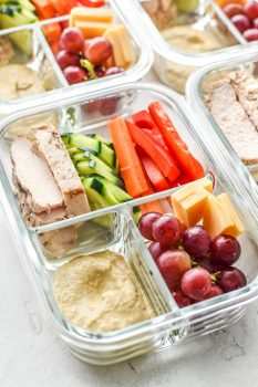 A Chicken & Hummus Plate Lunch Meal Prep with chicken, veggies and hummus ready to be eaten for lunch.