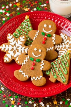 Gingerbread cookies on a red plate cut into gingerbread men shapes, trees and snowflakes. Decorated with royal icing and christmas sprinkles.