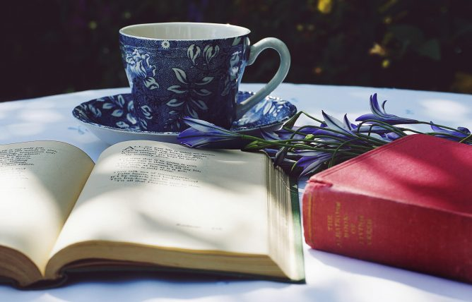 Book Opened on Top of White Table Beside Closed Red Book and Round Blue Foliage Ceramic Cup on Top of Saucer for World Poetry Day.