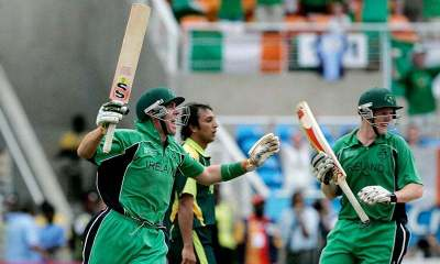 Two Irish players celebrating and a Pakistani player walking in the background with a sad face