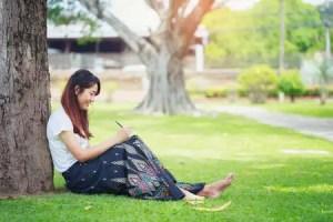 84635859 mujer joven sentada bajo un gran arbol y escribir su diario mujeres con concepcion natural