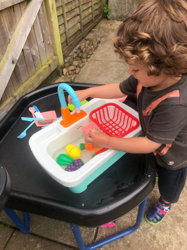 Toddler boy playing with a toy water sink in a tuff tray