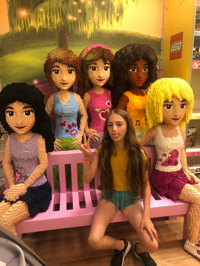 Ten year old girl sat with Lego friends models