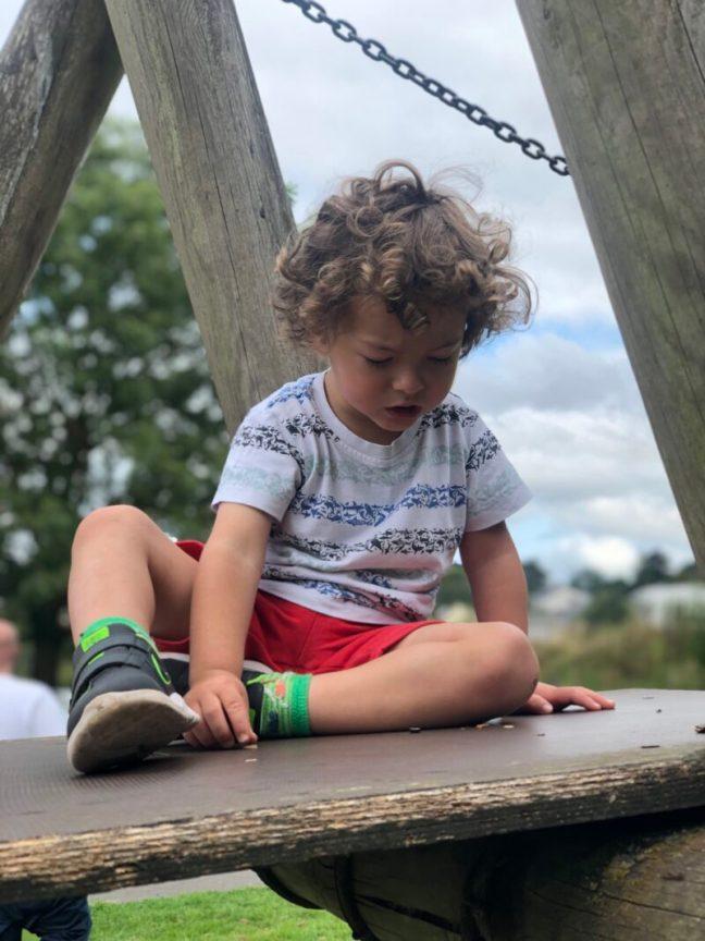 Toddler boy sat on a bridge at the park