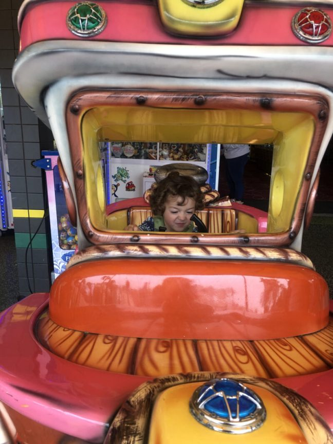 Toddler boy sitting on a ride at the Meuse entrance arcade